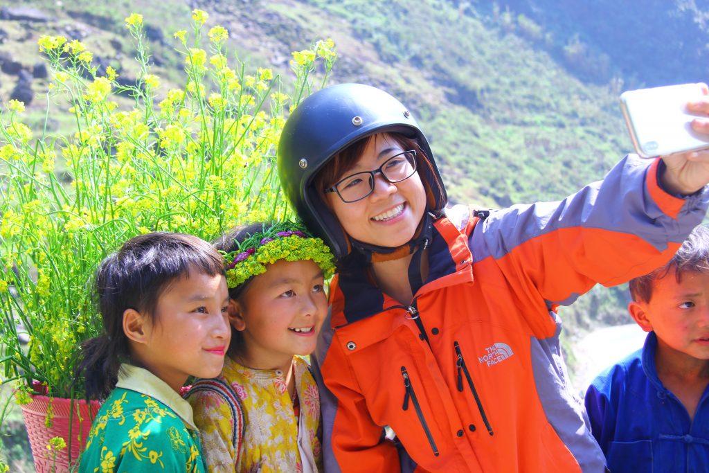 Ở trên đỉnh dốc có nhiều đứa trẻ địu trên mình những cái gùi hoa rực rỡ và rất đẹp.